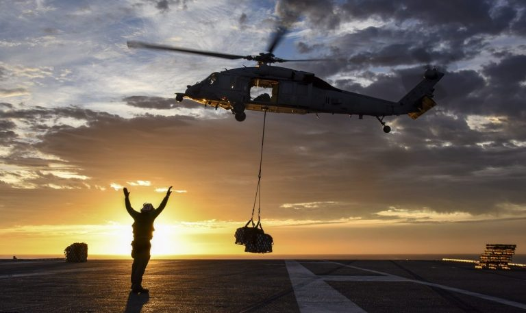 Helicopter dropping cargo on ship